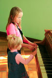 Piano de los juegos de las hermanas de las niñas Imagen de archivo