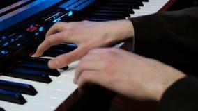 piano del gioco Chiuda su delle mani dell'uomo che giocano il piano al rallentatore Dita sul piano Esamini le mani di un pianista stock footage