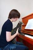 Piano del juego del muchacho y del gato Imagenes de archivo