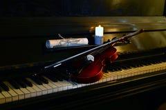Piano del violín por luz de una vela imágenes de archivo libres de regalías