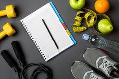 Piano di allenamento con l'alimento e l'attrezzatura di forma fisica su fondo grigio, vista superiore Immagini Stock