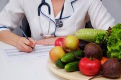 Piano di dieta di scrittura della donna del dietista sulla tavola in pieno della frutta e delle verdure Fotografia Stock