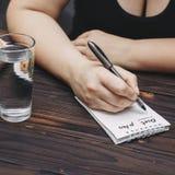 Piano di peso eccessivo di dieta di scrittura della donna nel libro della copia fotografia stock