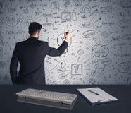 Piano di strategia di scrittura dell'uomo d'affari sulla parete Immagini Stock