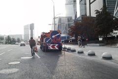Piano distante della bici atletica di guida dello sportivo su fondo urbano immagini stock libere da diritti