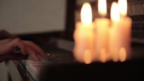 piano do jogo mãos fêmeas que jogam o piano da luz da vela Dedos no piano video estoque