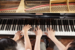 Piano duet. Two people, a couple playing piano duet, showing mostly their hands Royalty Free Stock Images