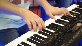Piano eléctrico, actor que juega en las llaves del piano del sintetizador del teclado El músico toca un instrumento musical en el metrajes
