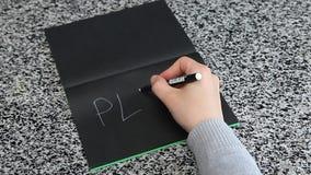 PIANO femminile di ortografia della mano sulla tavola situantesi di carta nera archivi video