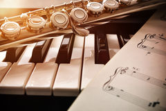 Piano and flute with golden shine and sheet music front Stock Photography