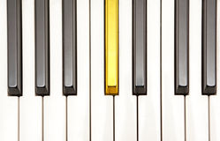 Piano with a gold key. Closeup of piano keys viewed from above Stock Image