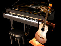 Piano and guitar. A classic guitar on a wooden chair, close to a grand piano, on a dark background Stock Photo