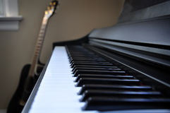 Piano and Guitar. Side view of a piano with an acoustic guitar in the background Royalty Free Stock Photo