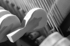 Piano hammer striking strings. Piano hammers striking strings from the side Royalty Free Stock Images