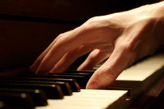 Piano Hand. A Caucasian male's hand playing a piano in dramatic lighting Stock Photos