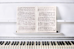 Piano hermoso blanco que brilla en el frente con las notas sobre un soporte Foto de archivo libre de regalías