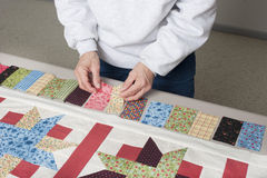 Piano key border layout. A quilter arranges fabric to assemble a piano key border to finish a quilt top Stock Photos