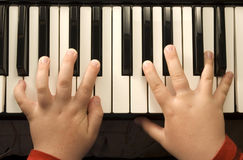 Piano Keyboard. Childs hands playing on a piano Keyboard royalty free stock photography