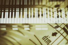 Piano keyboard background with selective focus. Double exposure of keyboard and musical notes Royalty Free Stock Photos