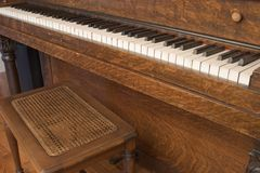 Piano Keyboard and Bench. Antique Oak Upright Piano Keyboard and Bench Royalty Free Stock Images