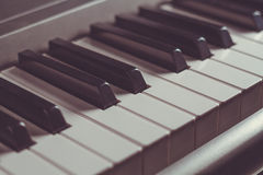 Piano keyboard, black and white keys close-up, retro toning. Piano keyboard, black and white keys close-up, musical instrument, retro toning, selective focus Stock Image