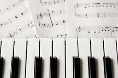 Piano keyboard on blured music-notes background. Top view Stock Photo