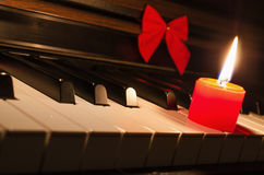 Piano keyboard with burning red candle and ribbon on it. Royalty Free Stock Images