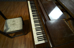 Piano Keyboard and Chair. Closeup view of the keyboard and chair of a grand piano Royalty Free Stock Photos