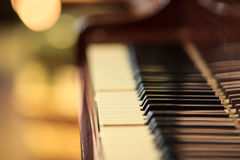 Piano keyboard. Closeup view of a piano keyboard with hazy bokeh on the blurred background. Mostly out of focus royalty free stock image