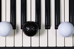 Piano keyboard and different golf balls and tees. Virtuosic game - Piano keyboard and different golf balls and wooden tees Royalty Free Stock Images