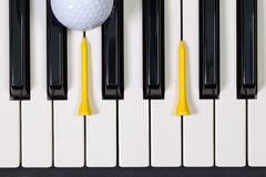 Piano keyboard and different golf balls and tees. Virtuosic game - Piano keyboard and different golf balls and wooden tees Royalty Free Stock Photo