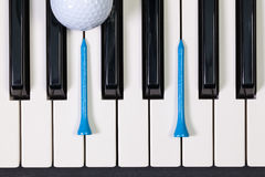 Piano keyboard and different golf balls and tees Stock Image