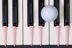Piano keyboard and different golf balls and tees. Virtuosic game - Piano keyboard and different golf balls and wooden tees Stock Image