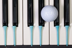 Piano keyboard and different golf balls and tees. Virtuosic game - Piano keyboard and different golf balls and wooden tees Stock Photography