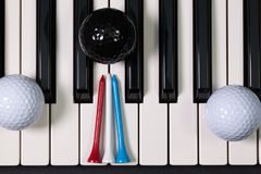 Piano keyboard and different golf balls and tees. Virtuosic game - Piano keyboard and different golf balls and wooden tees Stock Photos
