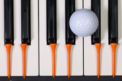 Piano keyboard and different golf balls and tees. Virtuosic game - Piano keyboard and different golf balls and wooden tees Stock Images