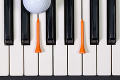 Piano keyboard and different golf balls and tees. Virtuosic game - Piano keyboard and different golf balls and wooden tees Royalty Free Stock Photos