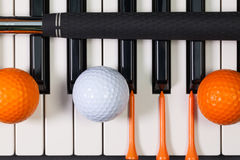 Piano keyboard and different golf equipments Royalty Free Stock Images