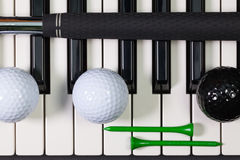 Piano keyboard and different golf equipments Stock Photo