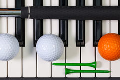 Piano keyboard and different golf equipments Royalty Free Stock Photos