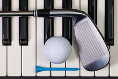 Piano keyboard and different golf equipments Stock Photography