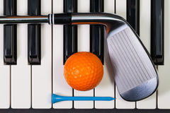 Piano keyboard and different golf equipments Stock Image