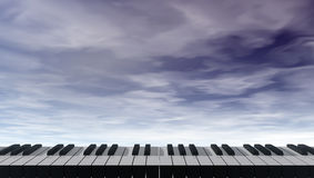 Piano keyboard in front of dark blue sky Stock Photo