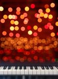Piano keyboard front view on lights bokeh background. Classical Piano keyboard front view on Christmas lights bokeh background royalty free stock photography