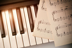 Piano keyboard with golden shine and sheet music top diagonal. Piano keyboard in diagonal with golden shine and sheet music. Horizontal Composition.Top view royalty free stock photography