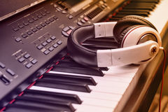 Piano keyboard and headphones. Headphones on piano keyboard with gradient purple and orange Stock Images