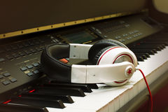 Piano keyboard and headphones. Headphones on piano keyboard with gradient purple and orange Stock Photography
