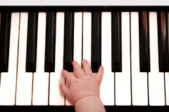 The piano keyboard and little child hand Royalty Free Stock Image