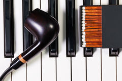 Piano keyboard and  luxury tobacco pipe Royalty Free Stock Photography