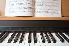 Piano keyboard and music book Stock Images